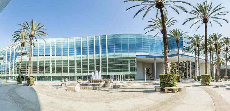 Exterior shot of a two-story building. The building is long, curved and predominantly glass. A fountain is visible in front of the building and palm trees are situated around the building.