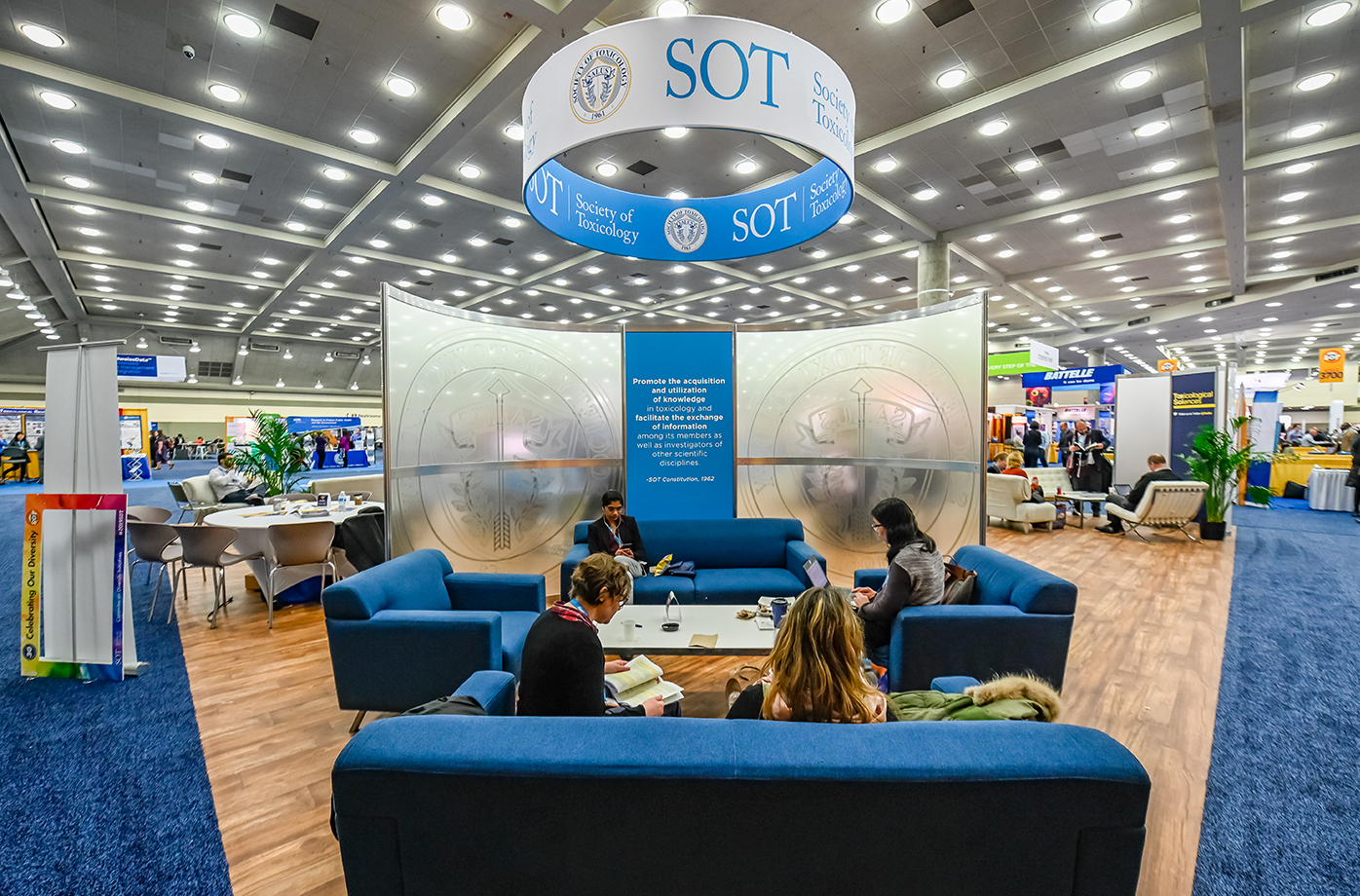 A large hollow sign reading 'SOT Society of Toxicology' is hanging from the ceiling. In the foreground are four blue couches with women in business attire sitting on them while reading and looking at their phones.
