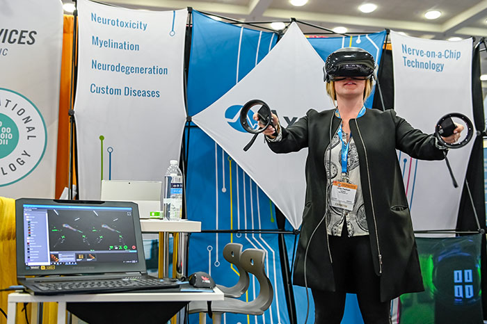 A woman stands in front of an exhibit booth facing the camera. Her eyes are covered with a virtual reality headset, and in each hand, she holds circular electronic devices. In the bottom left is a laptop displaying a microscopic, scientific image.