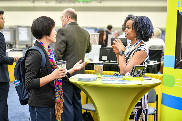 Two woman are talking while standing at opposite ends of a small, round, tall, yellow-green table. In the background, two gentlemen are having a conversation.