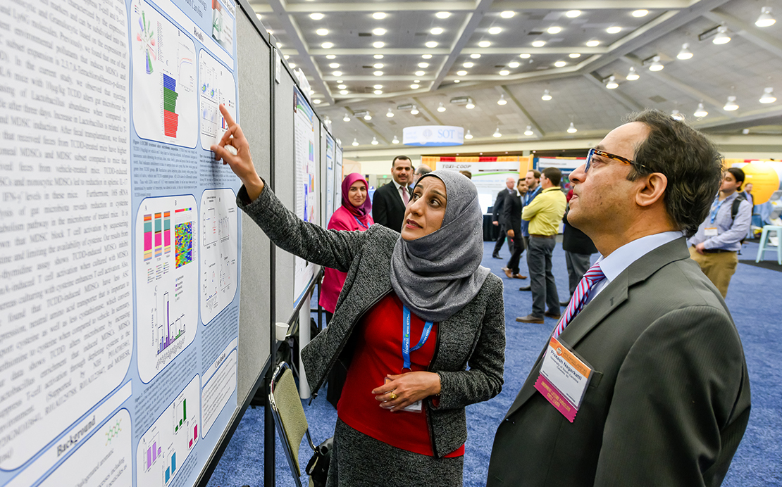 Running away from the camera is a long line of mounted posters. In the forefront, a woman in a hijab has her body facing the camera, but her face is turned toward the mounted poster on her right. She is pointing at a graphic on the poster with her right hand. Standing next to her in profile is a man looking at the item she is discussing. In the background, you can see other poster presenters and discussions.