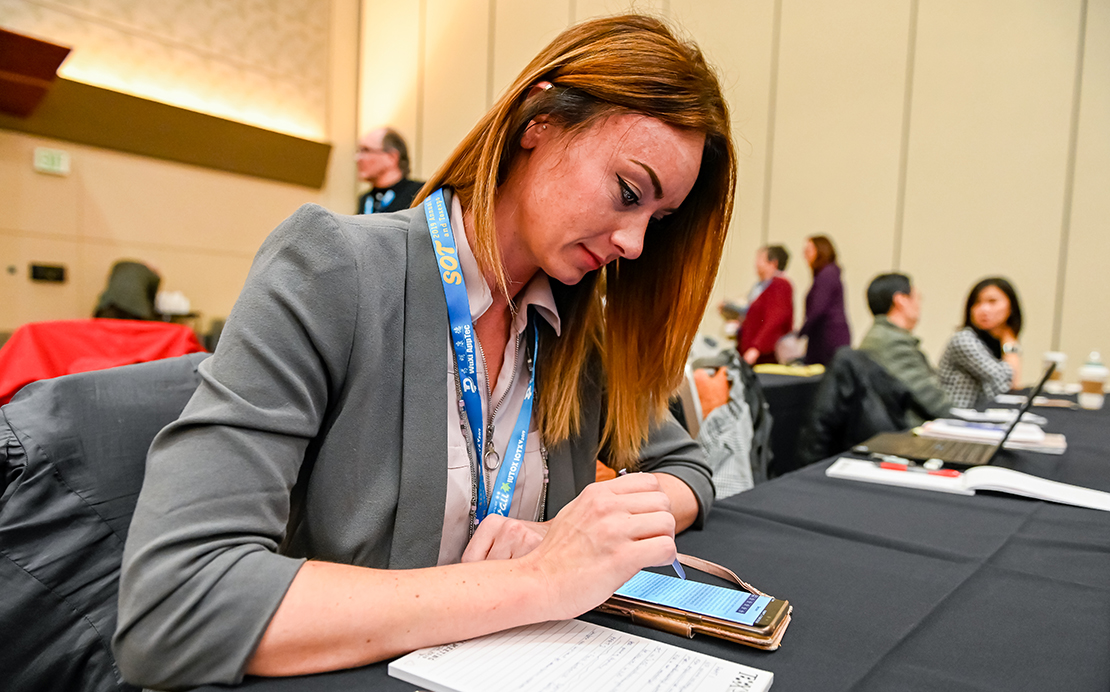 A woman sits at a table with a notepad and phone in front of her. She is using a stylus to work on her phone.