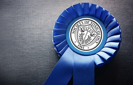 """A blue rosette ribbon is sitting on a gray background. The middle of the rosette contains the SOT Salus. The SOT Salus represents safety and protection from poison through increasing knowledge and is shaped in a circle. The border of the circle is a thick black line with a thinner black line along its inside. In a curve along the top half of the circle following the circle's edge are the words Society of Toxicology in all capital letters. Along the bottom of the circle is the date 1961 offset by two small hallow circles. Another circle border appears after this text ring. Inside this circle is a large shield touching the edges of this inner circle; this shield represents protection. Filling the space outside the shield and within the inner circle are radiating straight lines meant to depict force manifesting itself. Placed vertically in the center of the shield is a feathered arrow with the point pointing to the top of the shield/circle; the arrow is meant to symbolize """"toxicum"""" or the poisoned arrow. Appearing beside the feathers at the bottom of the arrow are two wreath strands which symbolize success. Below the point of the arrow is a ribband containing the word Salus in all capital letters; the ribband denotes pre-eminence while Salus is Latin for safety."""