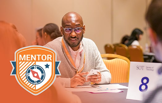 A black man sits at a table. He appears to be in conversation with unseen individuals at his table. Overlaid on the photo is a graphic of a orange and blue shield/badge that reads MENTOR.