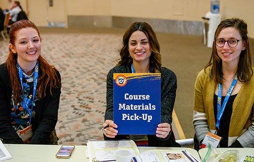 Three young women are sitting at a table, looking at the camera, and smiling. The one in the middle is holding a sign that reads Course Materials Pick-Up.